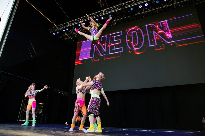 A group of people throw a woman into the air in a straddle position. They are all wearing fluro.