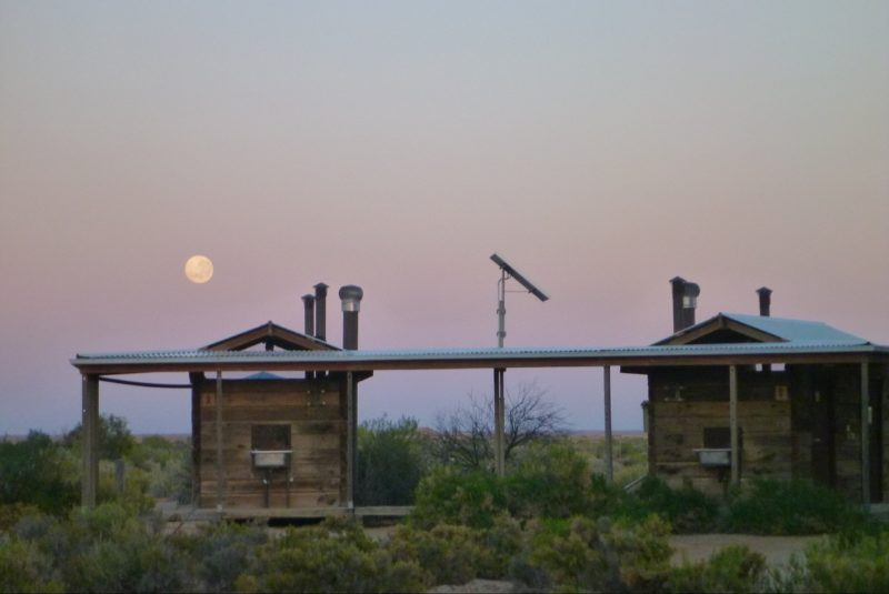 The full moon or the setting sun are framed by the walkway of the railway sleeper toilet block