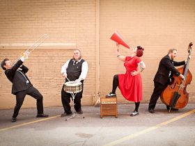Davina in a red dress & the Vagabonds infront of a brick wall playing instruments
