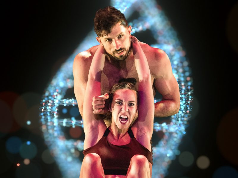 A female acrobat with a fierce expression is suspended on a male acrobat. A DNA helix swirls behind.