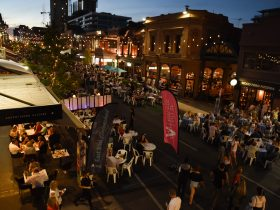 Street party in Rundle St, Adelaide. Lots of people, festoon lighting, buildings at dusk. Summer.