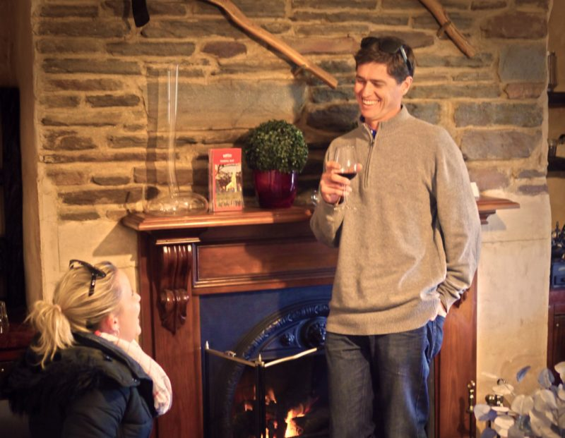 People drinking wine in front of a fireplace