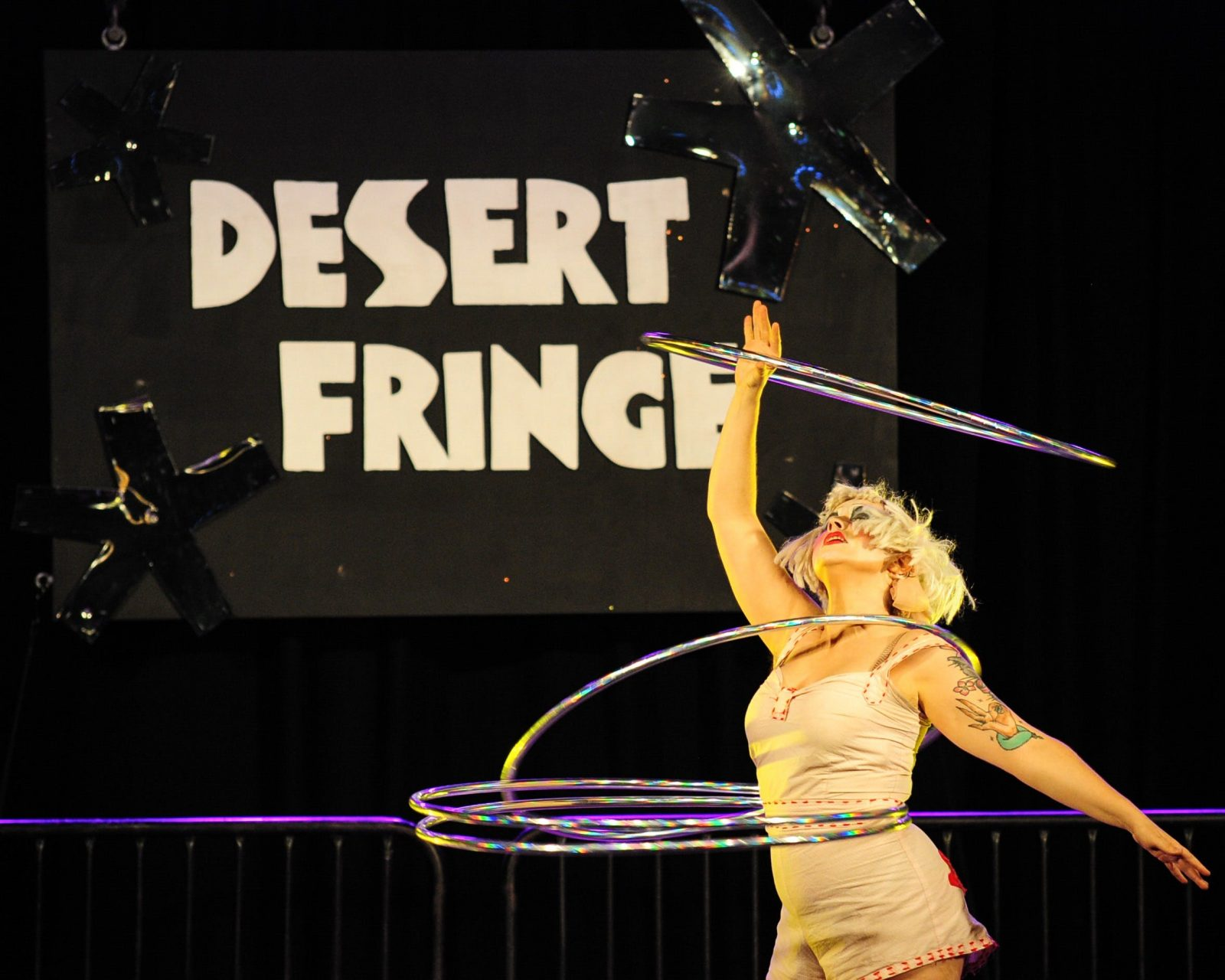 A performer is spinning many hoops around their body and arm in front of a Desert Fringe sign