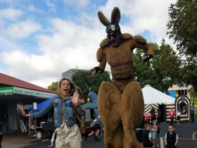 A performer in a kangaroo suit with stilts and a person jumping in the air