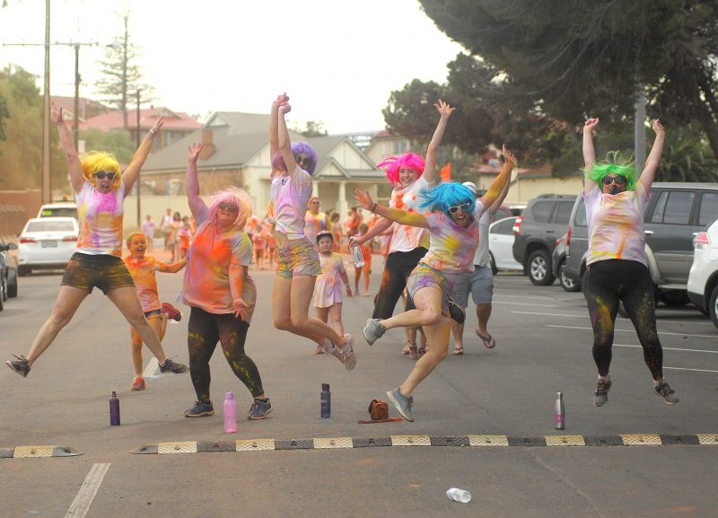 A group of people dressed in white with chalk paint and coloured wigs jumping in the air