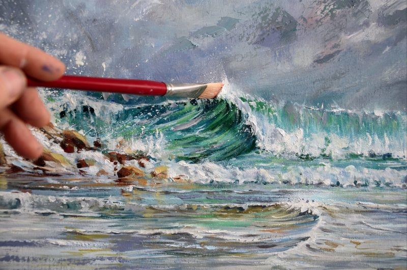 Close up shot of Paul Whitehead painting a wave in oil