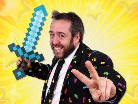 Matty Grey holds a Minecraft diamond sword while smiling at the camera and holding up two fingers