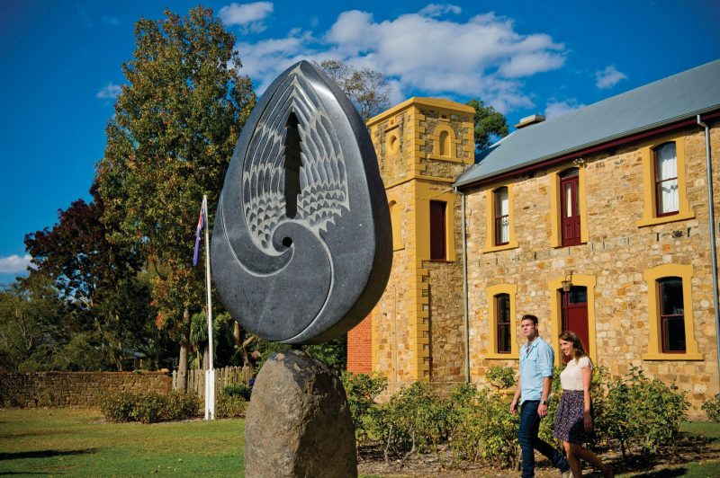 Stone sculpture in front of heritage building with couple walking past in Hahndorf's main street