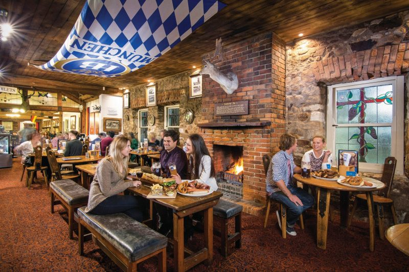 Friends sitting at table with German food in front of an open fire in heritage pub - Hahndorf Inn