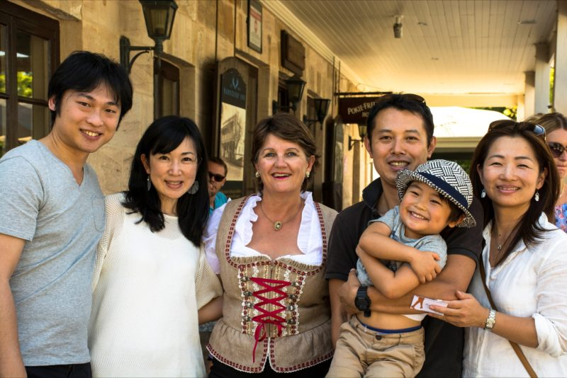A group of Chinese visitors on a Hahndorf Walking Tour, laughing and smiling