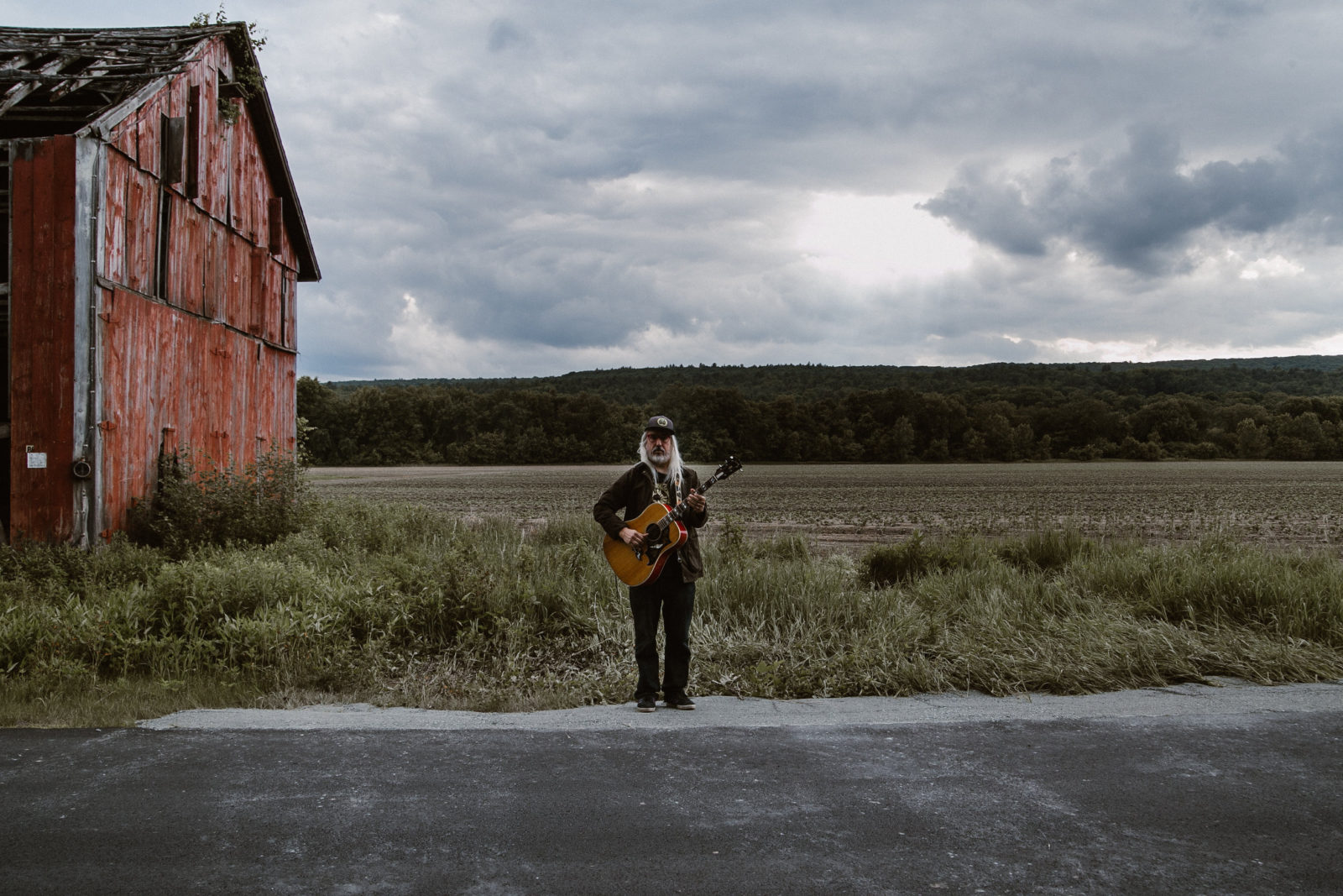 J Mascis standing, holding his guitar in a field by an old barn