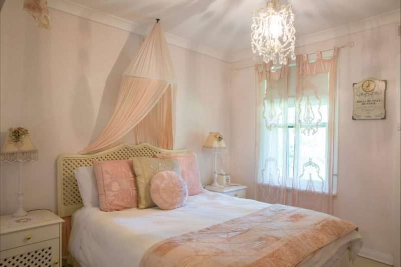 Powder puff pink shabby chic queen size bedrooms with soft velvet curtains.