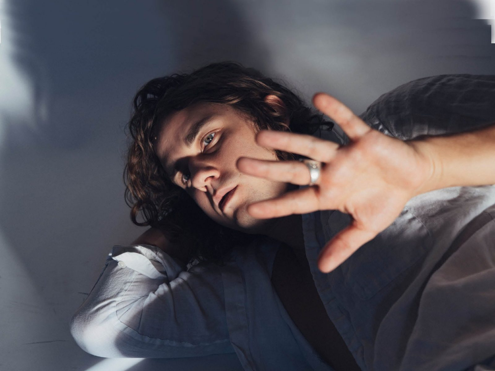 Headshot of Kevin Morby with his hand covering half his face
