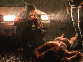A man squats in the light of a car's headlights over a body as it rains
