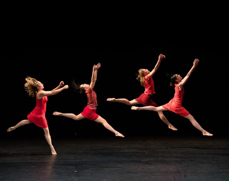 Dancers from Lyon Opera Ballet dressed in red against black background
