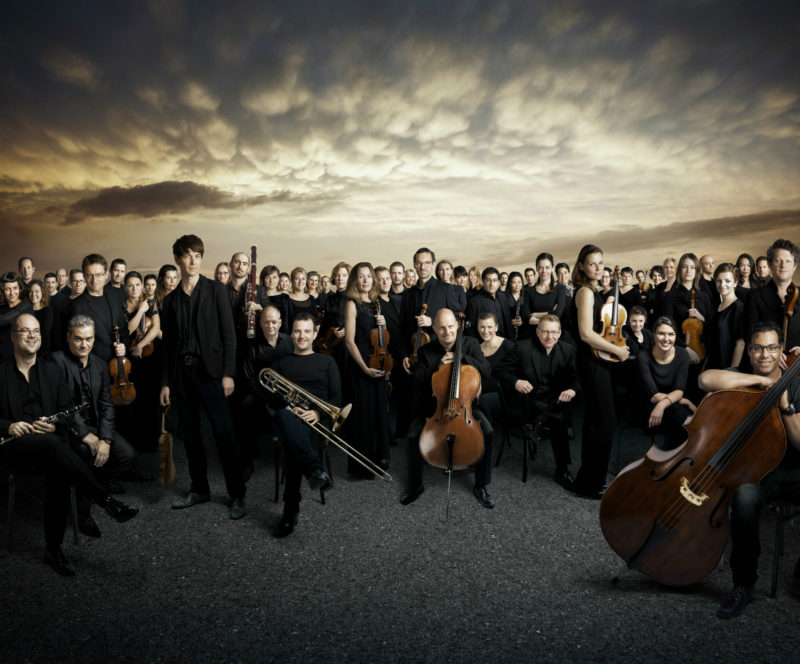 The Mahler Chamber Orchestra sit in a semicircle with their instruments