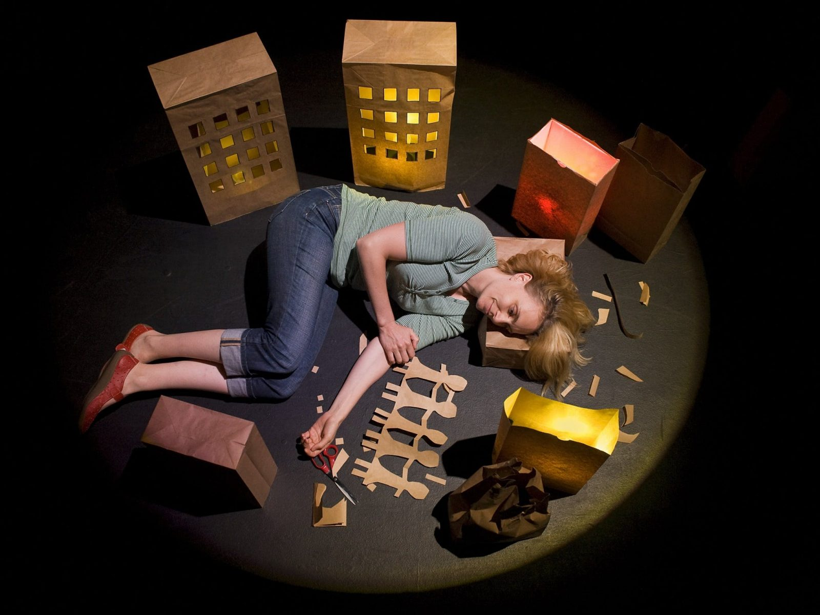 A woman lays curled on the floor surrounded by paper houses