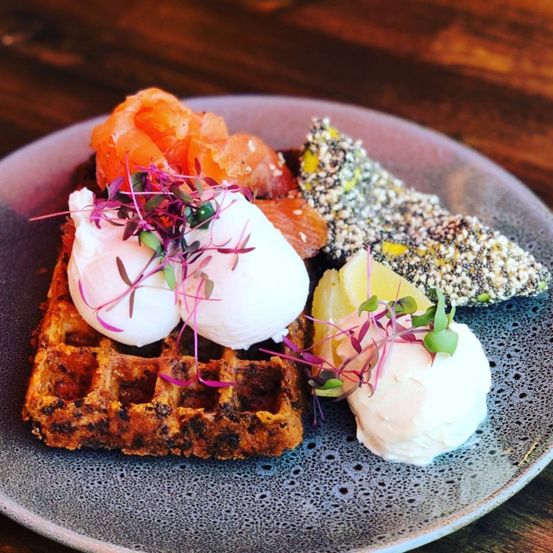 Cauliflower and cheese waffles with smoked salmon, avocado, poached eggs and sour cream