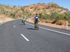 4 cyclists descending a range with red cliffs