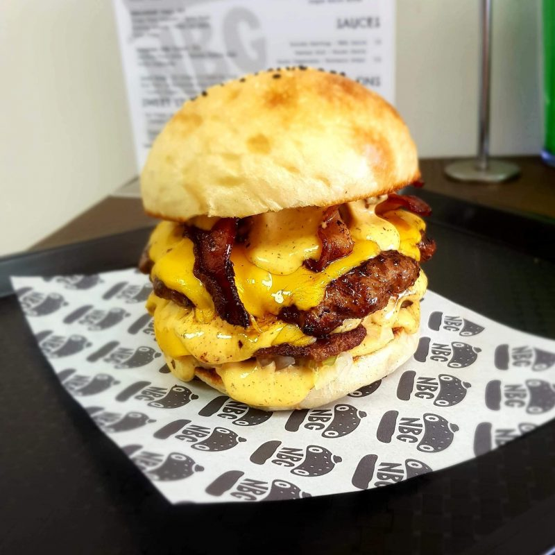 Two succulent beef patties, double cheese, double hickory smoked bacon and NBG house sauce