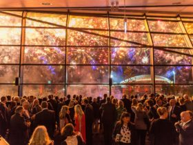 A crowd of people watch a fireworks display through large glass windows at the Convention Centre