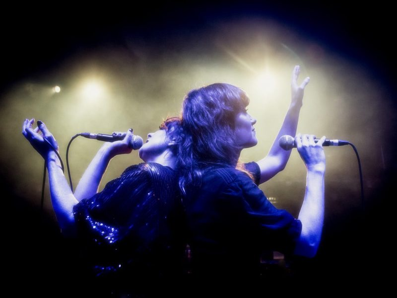 Nouvelle Vague on stage holding microphones