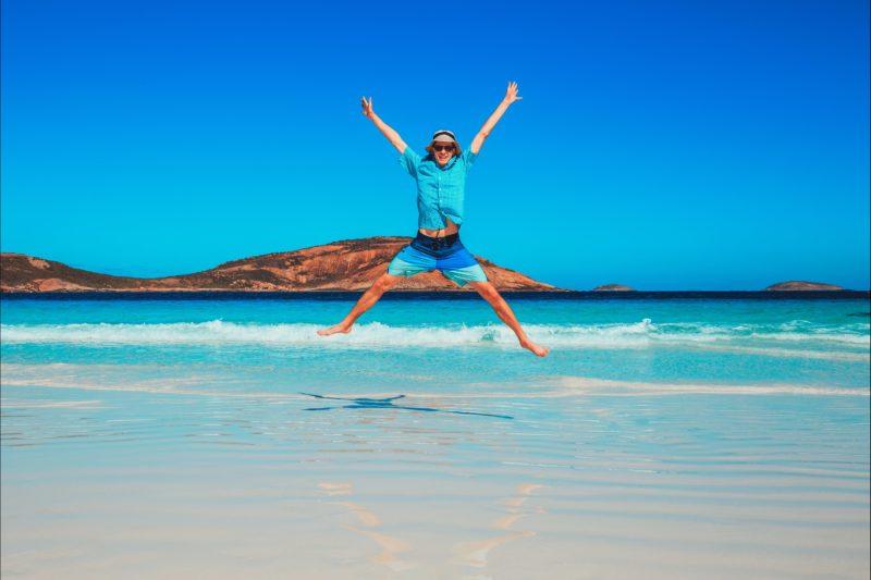Guy jumping on white sandy beach