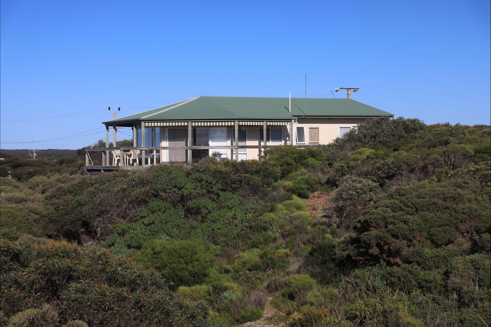 View of house set high amongst surrounding coastal vegetation