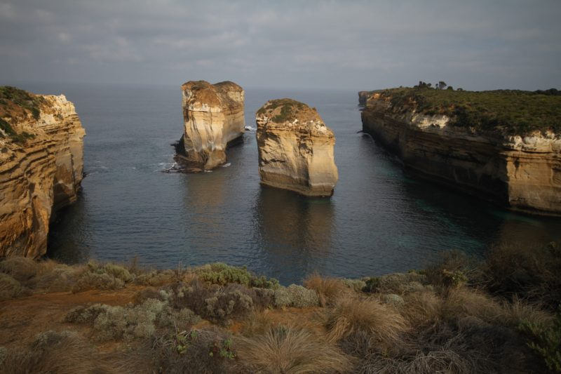 two sandstone pillars standing in the sea just off the coast on the great ocean road