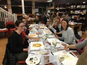 Group of smiling people enjoying painting, wine and food