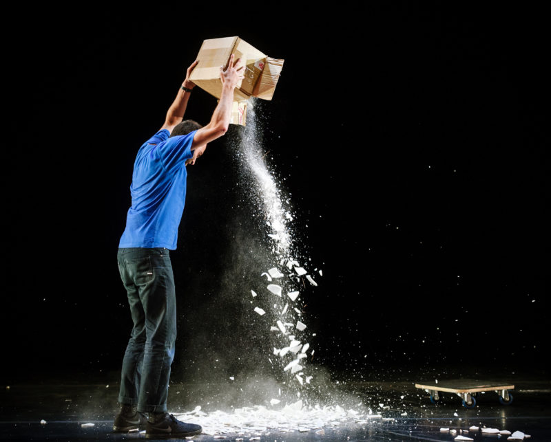 A man empties a box and the contents are shattering on the ground
