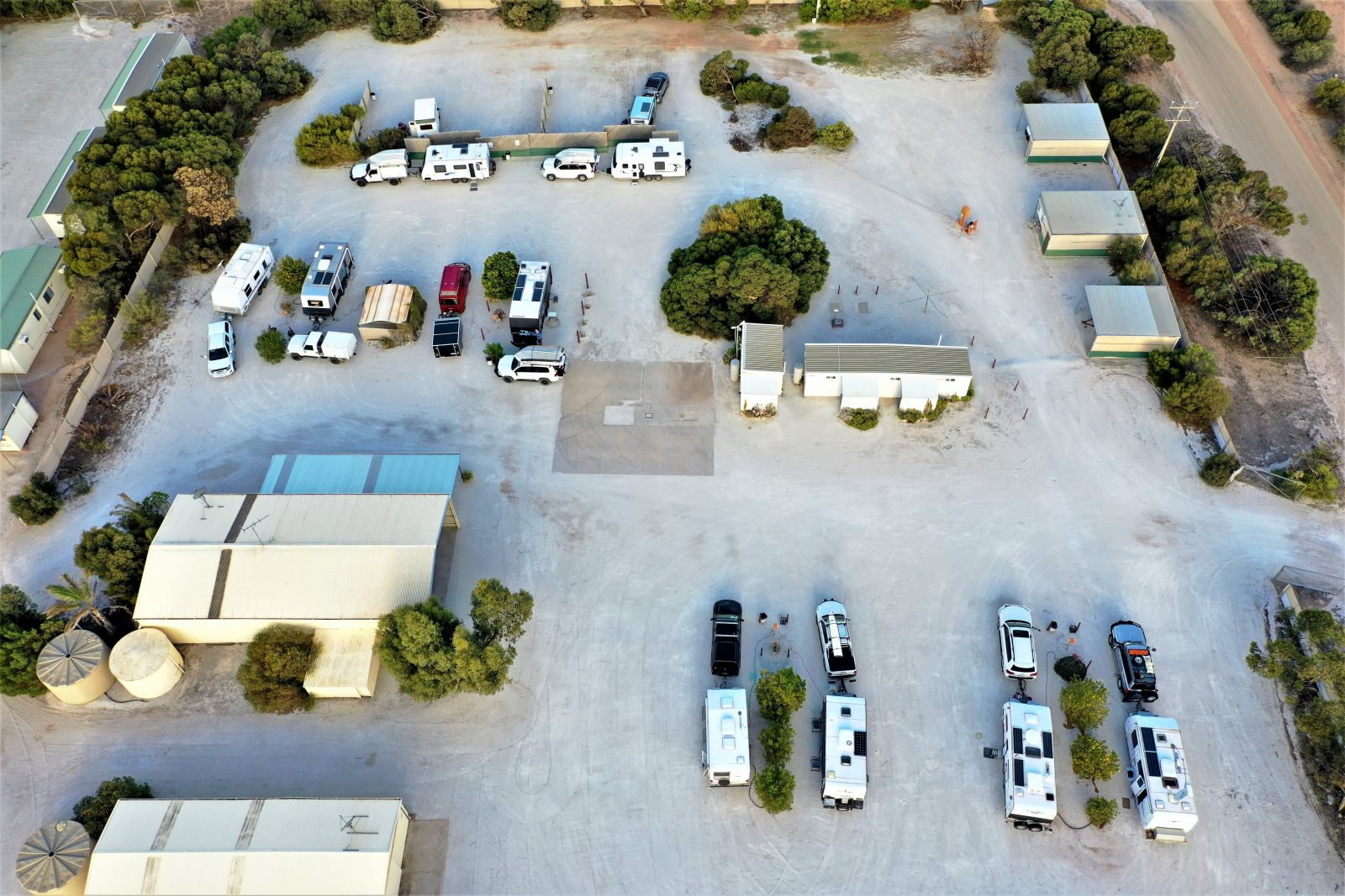 Penong Caravan Park fro the air with vans and facilities. Spacious, clean white gravel with trees.
