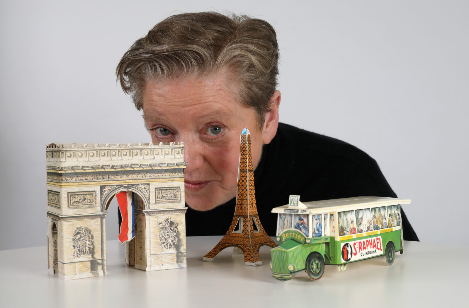 Image of Robyn Archer peering from behind three models of a bus, Eiffel Tower and Arc De Triomphe