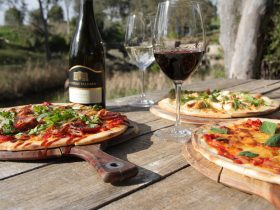 Pizzas & glasses of wine set by the creek
