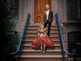 Julia Zemira in a red dress and Brian Nankervis in a suit in front of a New York City brownstone