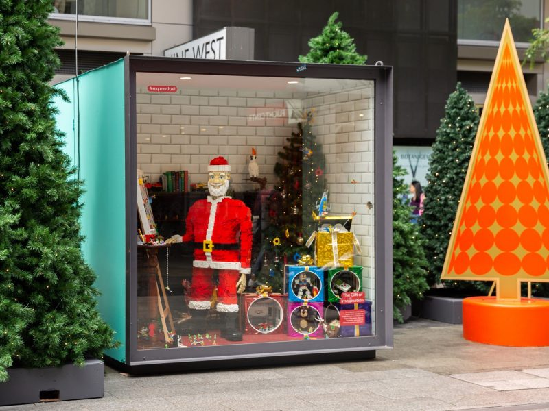 Santa made from LEGO bricks with LEGO dioramas of Christmas presents with elf minifigures