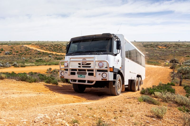 large 6WD coach driving on a dirt road