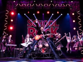 A rock band with students dressed in uniform is performing on stage.