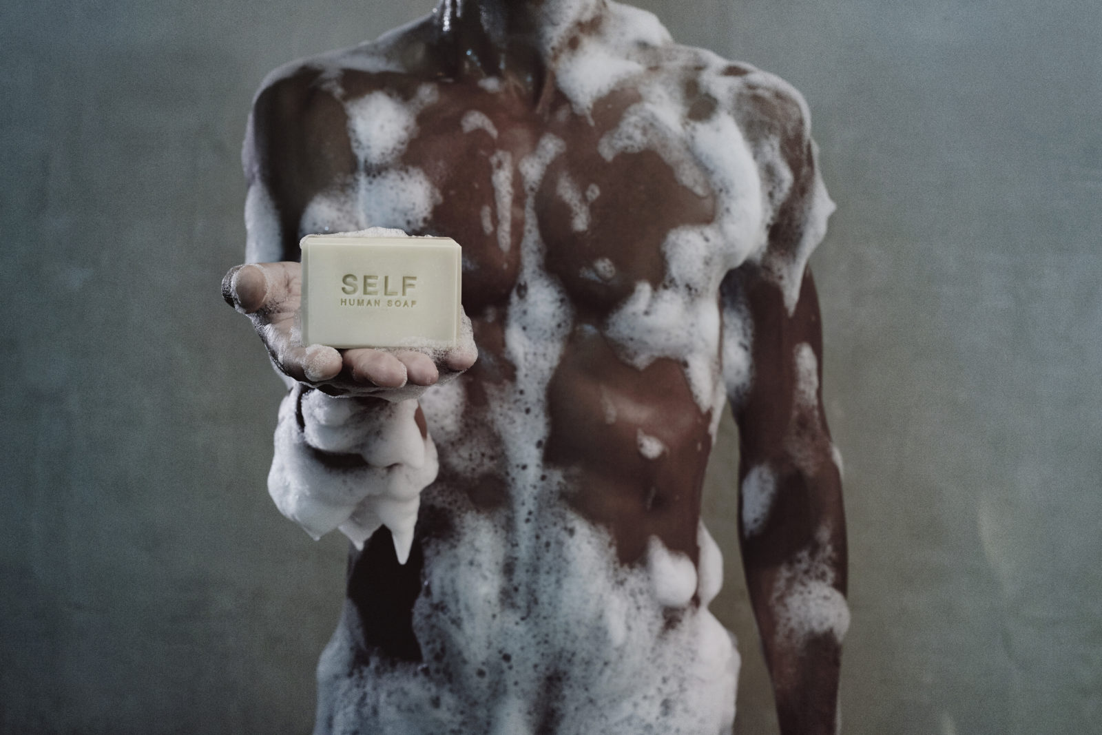 A man, lathered up with suds, holds a bar of soap in front of him