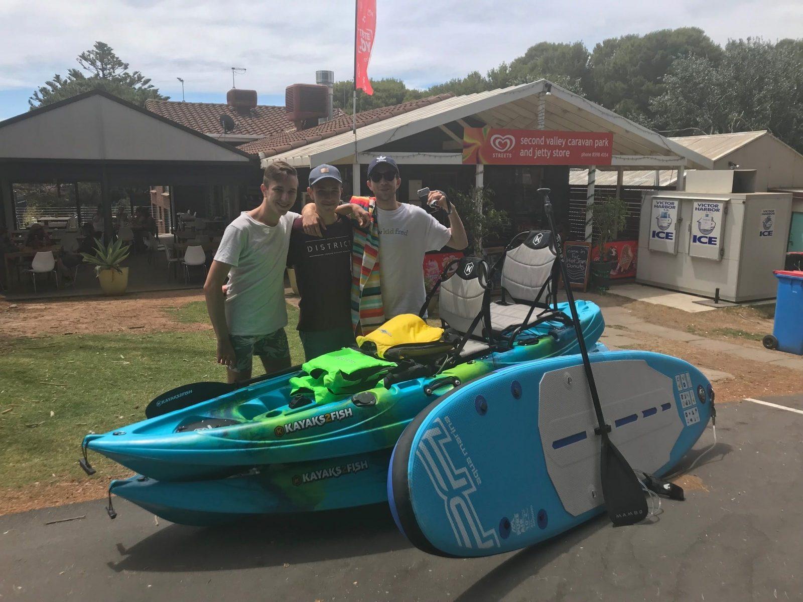 People standing next Kayaks