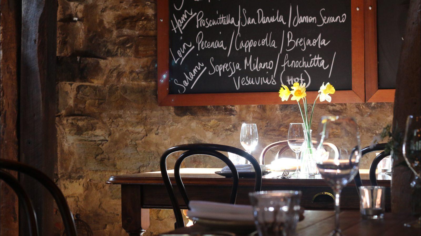 old stone walls, elegant dining table, blackboard menu of cured Italian meats. sunlight & daffodils