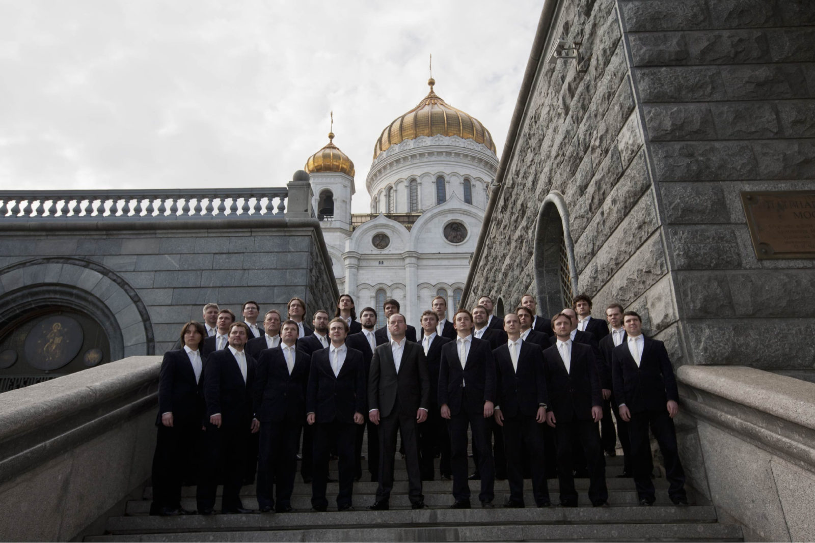 The Sretensky Monastery Choir stands on stairs with a Russian building behind them