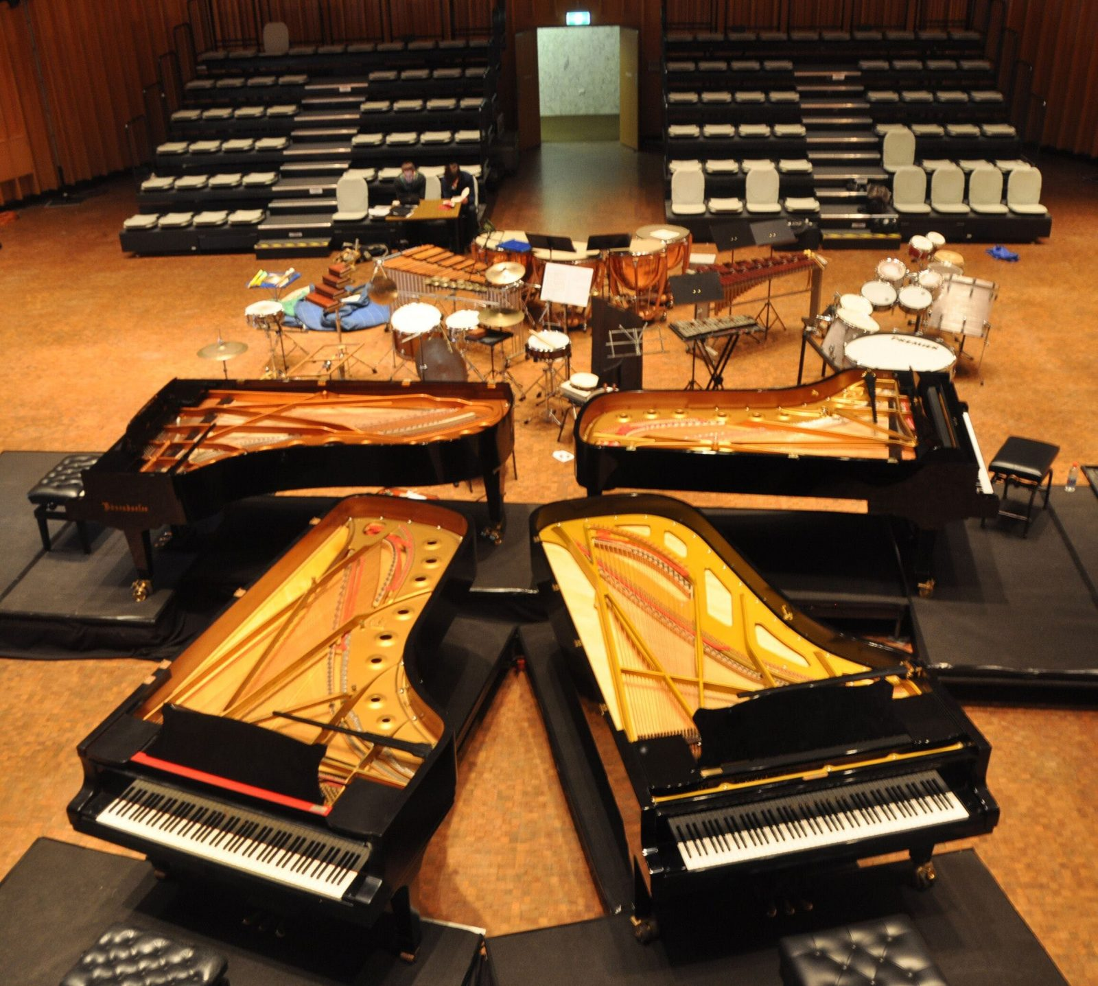 4 grand pianos, drums and various percussion instruments in a concert hall