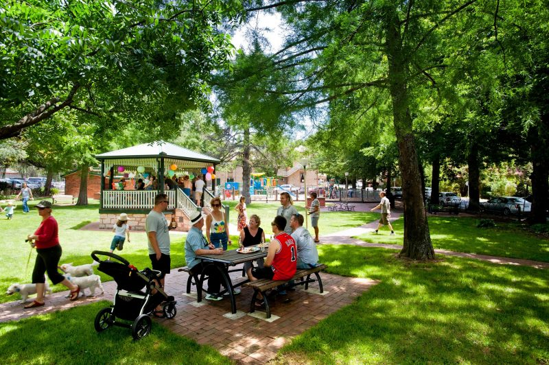 Family at picnic table with pusher, rotunda and playground surrounded by green trees and grass