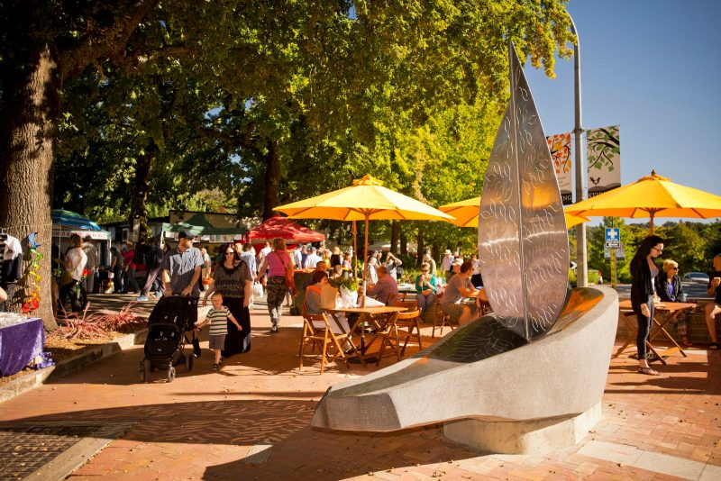Stone and metal boat sculpture, with green trees, people sitting at tables under yellow umbrellas
