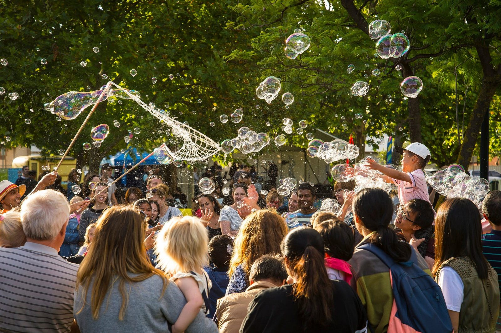 Group of adults watching children blow bubbles, take part in a bubble show and enjoy themselves.