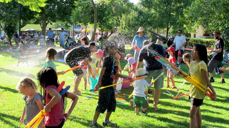 Group of children playing with water pistols and water activities while parents watch.