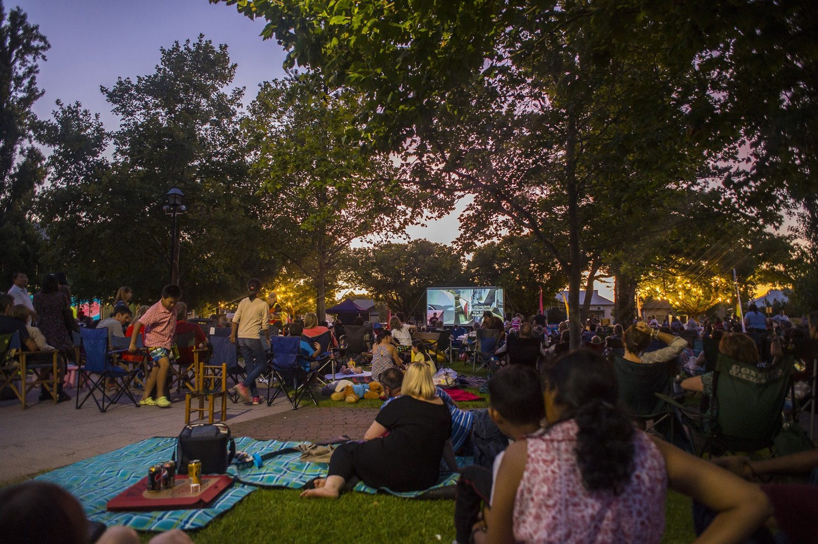 Group of people watching movie in park during the evening.