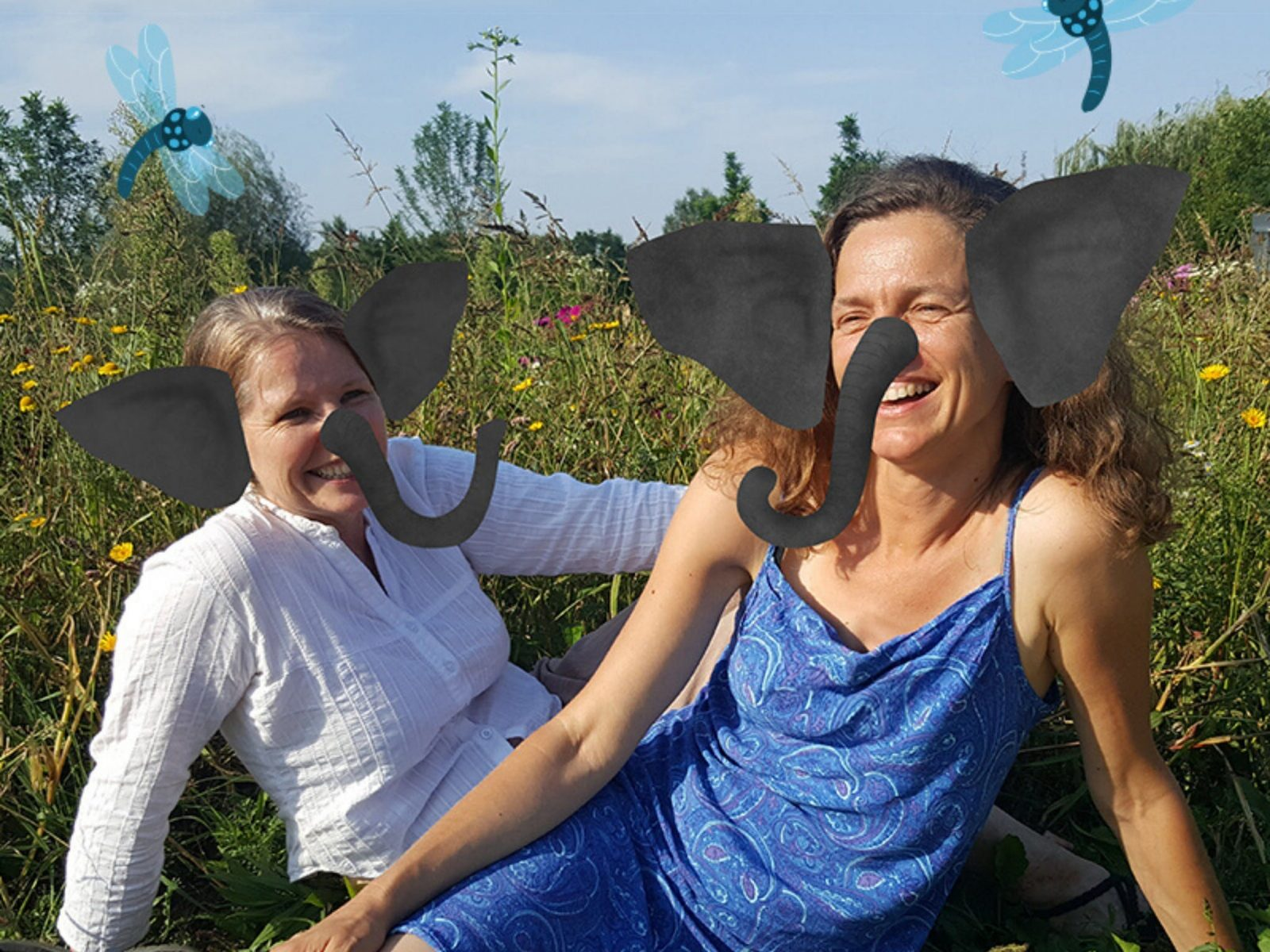 Two women sit in a field, with elephant ears and trunks on their faces.