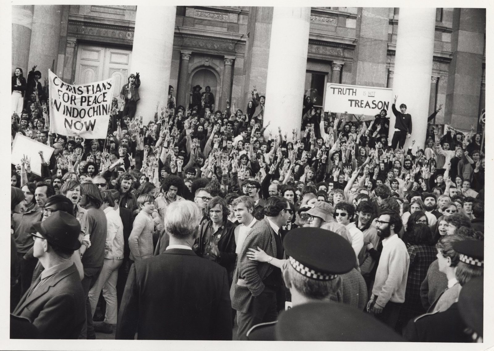 A crowd of people holding protest signs on the steps of a big building with columns